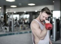 man-in-white-tank-top-holding-red-kettlebell